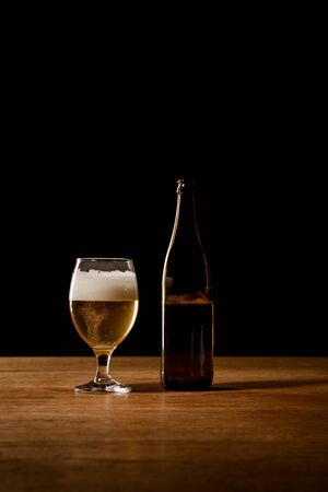 beer in bottle and glass on wooden table isolated on black