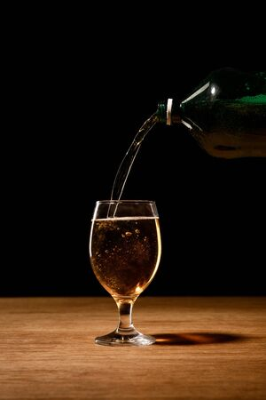 beer pouring from bottle in glass on wooden table isolated on black