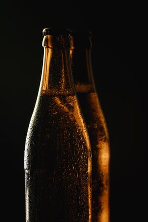 glass bottles of beer with water drops isolated on black