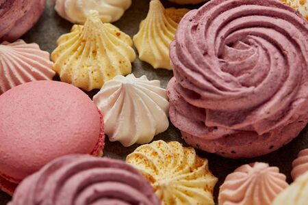 Small sweet meringues with pink soft zephyr and pink french macaroons