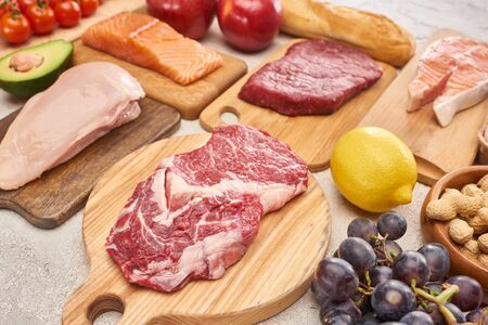 Fresh raw meat, poultry, fish on wooden cutting boards near lemon, grapes, apples, branch of cherry tomatoes, nuts and french baguette on marble surface