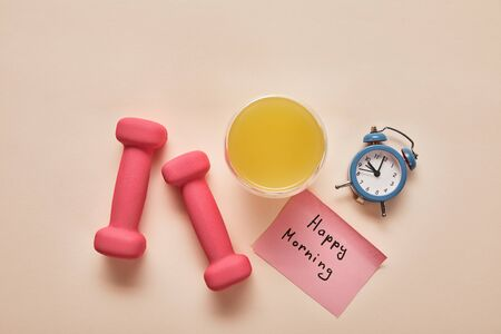 top view of sticky note with happy morning lettering, pink dumbbells, orange juice and small alarm clock on beige background Reklamní fotografie