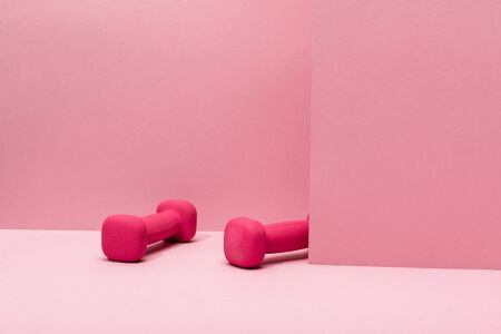 pink bright dumbbells levitating in air on pink background