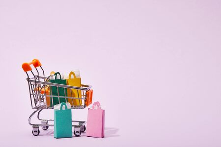 few shopping bags near toy decorative cart with colorful paper bags on violet
