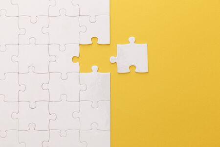 노란색 배경에 흰색 직소 퍼즐의 상위 뷰 스톡 콘텐츠