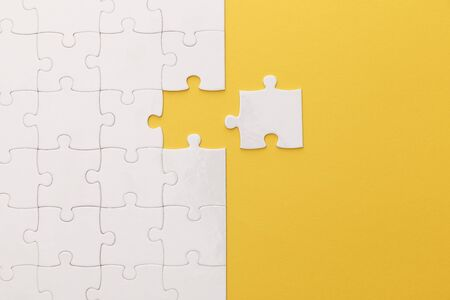 top view of white jigsaw puzzle on yellow background