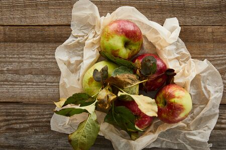 top view of ripe apples with leaves on creased parchment paper on wooden surface Stock fotó - 130575507