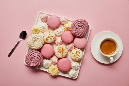 Top view of  meringues and macaroons on square dish with spoon and cup of tea on pink background
