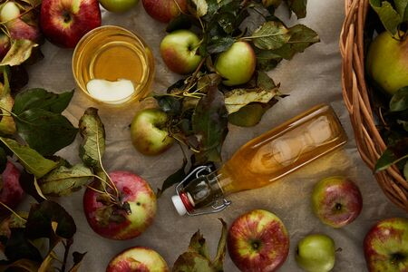 top view of bottle and glass with cider near apples and wicker basket Imagens