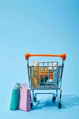 few small paper bags near toy cart with colorful shopping bags on blue background Imagens