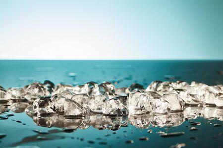 fresh melting ice cubes on emerald and white background