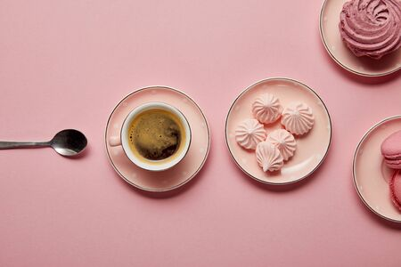 Top view of pink meringues and macaroons on pink dotted saucers with spoon and cup of coffee on pink background