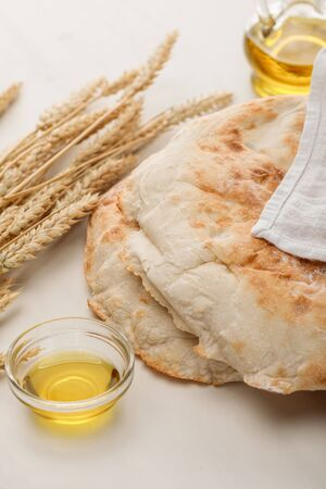 lavash bread covered with towel near spikes and oil on white surface Stock Photo