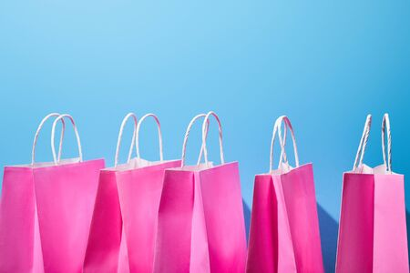 few pink paper shopping bags with white handles on blue background