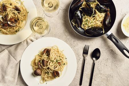 top view of delicious pasta with seafood served with white wine and napkin on textured grey surface