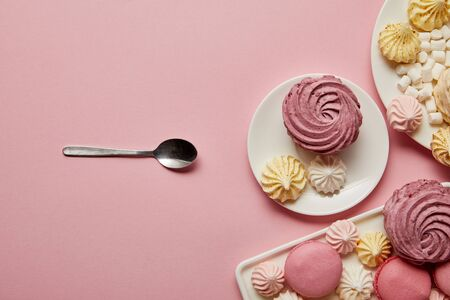 Plates with sweet meringues and macaroons with spoon on pink background