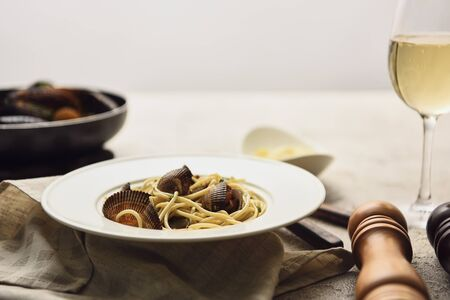 selective focus of delicious pasta with seafood served with white wine on napkin isolated on grey