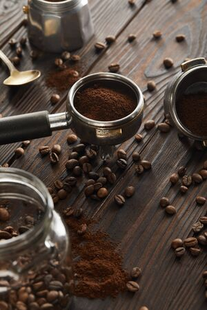 Portafilter near spoon, geyser coffee maker and glass jar with coffee beans on dark wooden surface 스톡 콘텐츠