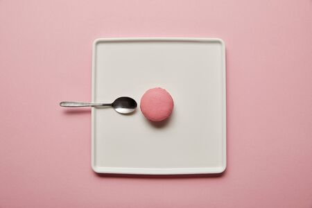 Top view on pink macaroon with teaspoon on white square dish on pink background