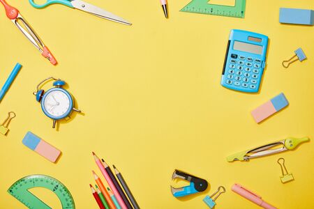 top view of school supplies scattered on yellow background with copy space