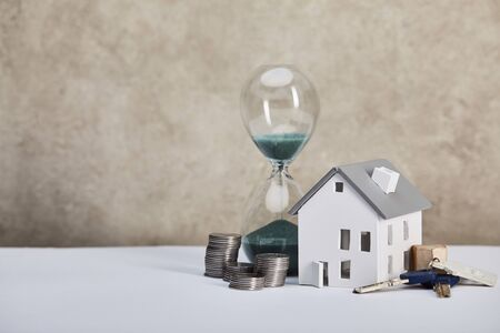 house model on white table with hourglass, coins and keys, real estate concept 写真素材