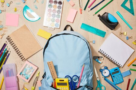 top view of various school supplies with blue backpack on wooden desk