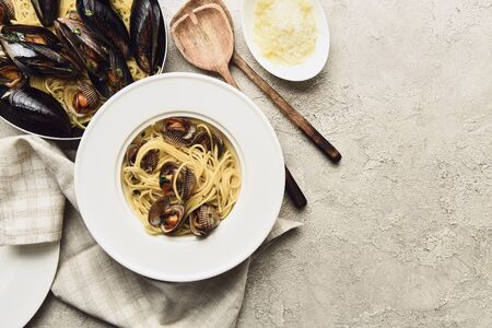 top view of tasty pasta with seafood and grated cheese on weathered grey background with copy space Banco de Imagens