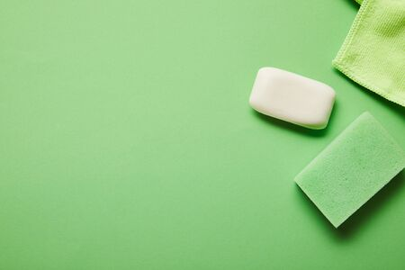 top view of white soap, rag and sponge on green background Stock Photo