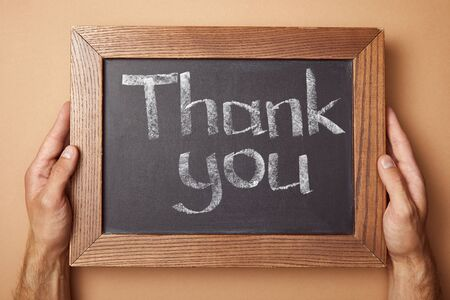 cropped view of man holding chalkboard with thank you lettering Stock Photo