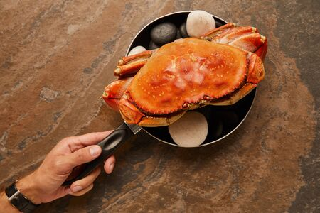 cropped view of uncooked crab with solid shell with black stones in frying pan on textured surface Banco de Imagens