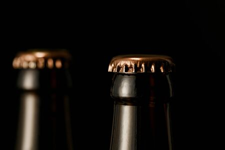 close up view of glass bottles of beer with metal caps isolated on black Stock Photo - 130602113