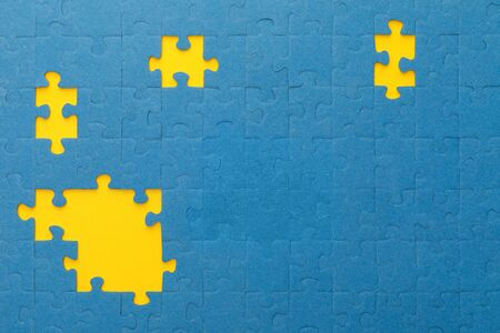 top view of blue jigsaw puzzle with yellow gaps