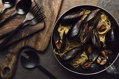 top view of delicious pasta with mollusks and mussels in frying pan near wooden cutting board with black cutlery