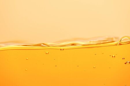 ripple yellow bright liquid with splash and bubbles isolated on yellow