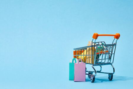 few small paper bags near toy cart with colorful shopping bags on blue