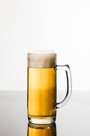 glass of beer with foam isolated on white