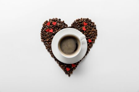 top view of coffee in cup on saucer with heart made of coffee grains on white background