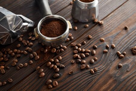 Geyser coffee maker near portafilter on dark brown wooden surface with coffee beans 스톡 콘텐츠