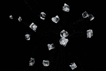top view of scattered transparent refreshing ice cubes isolated on black