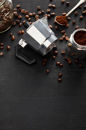 Separated parts of geyser coffee maker near glass jar and spoon on dark wooden surface with coffee beans 스톡 콘텐츠
