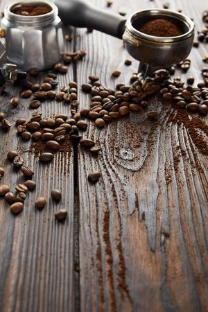 Portafilter near geyser coffee maker on dark wooden surface with coffee beans 스톡 콘텐츠