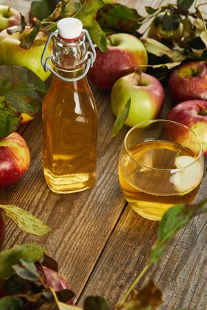 bottle and glass of fresh cider on wooden surface with ripe apples