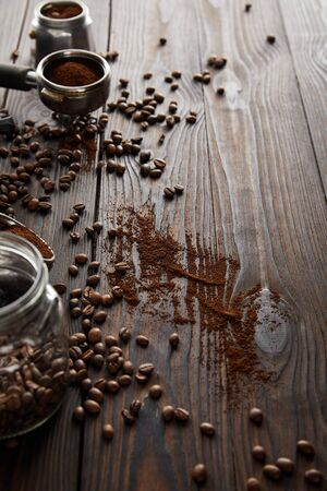 Glass jar near portafilter and part of geyser coffee maker on dark wooden surface with coffee beans