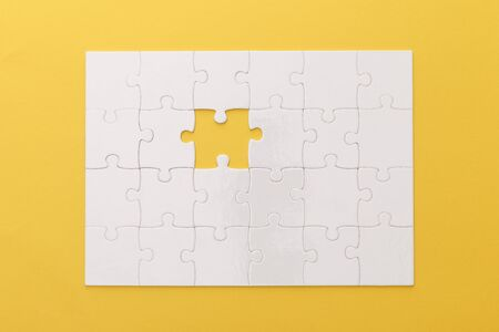 top view of white jigsaw puzzle with lost piece on yellow background Stock Photo
