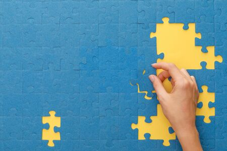 cropped view of woman matching blue jigsaw puzzle on yellow background