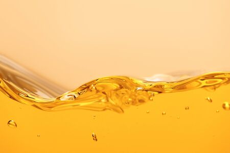 curved yellow bright liquid with splash and bubbles isolated on yellow Stock Photo