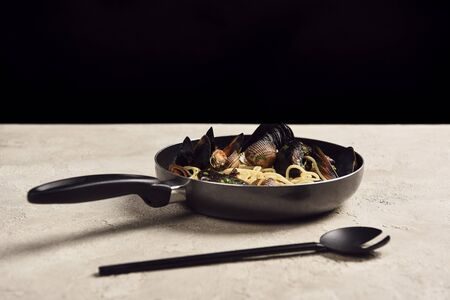 delicious Italian pasta with seafood served in frying pan near spatula isolated on black
