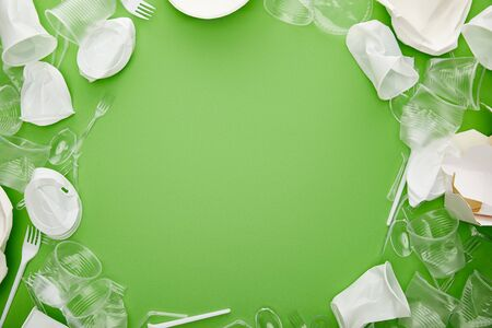top view of crumpled plastic cups, forks, plates and cardboard container on green background with copy space 版權商用圖片