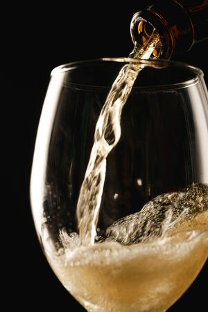 beer flowing from bottle into glass with splash isolated on black Stock Photo - 130575702