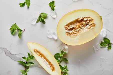 Draufsicht auf geschnittene köstliche Melone mit Samen auf Marmoroberfläche mit Minze und Eis
